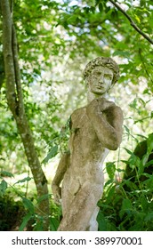 Man Statue. Male stone sculpture in classical style with green foliage background