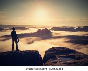 Man stay with red cap on rocky peak. Man walking over rocky summit to Sun. Beautiful moment the miracle of nature. Vintage effect