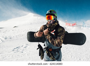 man stay with snowboard equipment on the snow hill