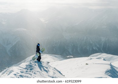 man stay and watch beautiful view with snowboard equipment