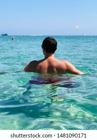 Man is staying in the blue water, summer relax and fun.