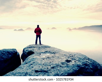 Man is  staying on a top of a rock above clouds. Man on mountain.  Conceptual design.