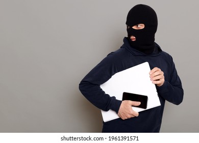 Man steals laptop and phone, runs away and turns back, being of persecution, wears robber mask and black turtleneck, advertising space, isolated over gray background.