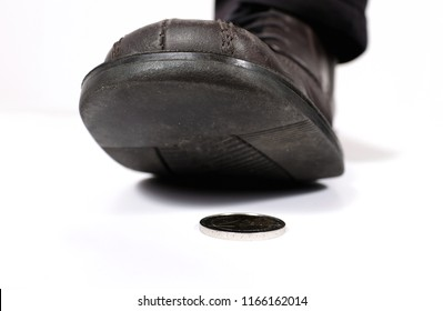 A man stealthily steps on a coin lying on the floor