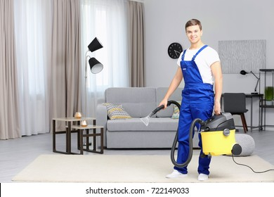 Man with steam vapor cleaner in living room