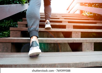 A man step up to success, sport man is climbing on wooden step