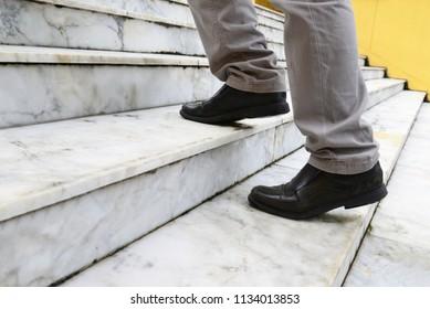 man step walking up marble stair