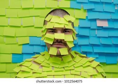 Man with stickers on his face against the wall in stickers. A lot of stickers are glued in order not to forget important information.