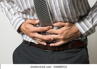 A man with a stomach ache. Unhappy people suffering. White background, Concept with Healthcare And Medicine.