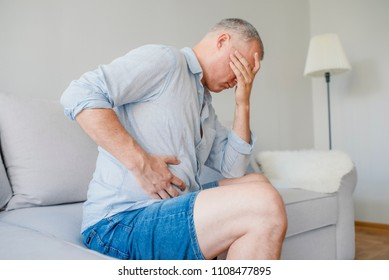 Man stomach suffering from stomachache or Gastroenterologist. Concept with Healthcare And Medicine. Unhappy man suffering from stomach ache at home