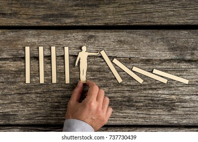 Man stopping the domino effect with a paper cutout silhouette on a rustic wood background.