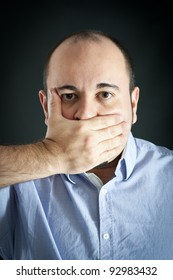 Man stopping up the mouth on dark background.