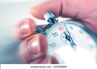 man stopping a stopwatch with motion blur