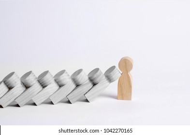 Man stops falling dominoes. Dominoes of people fall on one strong person. The concept of a bold, strong and decisive person. Strong business. Place for text. Wooden figurines.