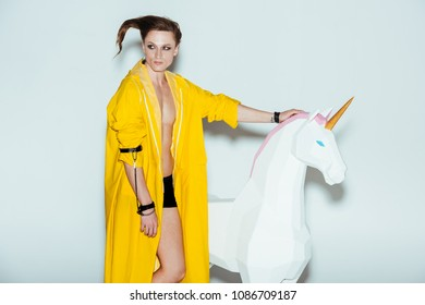 man with strange hairstyle in yellow raincoat standing with big unicorn toy, on grey