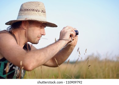 The man in a straw hat with the camera has a rest outdoors