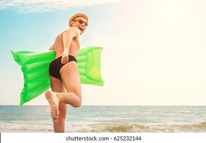 Man in straw hat runs with air swimimg mattress in the sea
