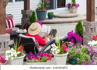 Man in a straw sunhat sitting on a recliner chair relaxing reading on an outdoor patio viewed across colorful potted summer flowers on the wall