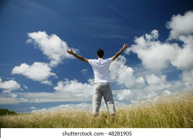 Man stretching arms up in the middle of a field