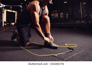 Man stretching up and getting ready to powerful workout on jump rope in boxing sport gym