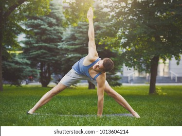 Man stretching hands and legs on green grass in park. Athlete do workout outdoors. Sport, yoga, pilates, fitness, healthy lifestyle concept