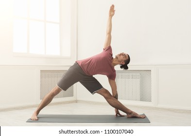 Man stretching hands and legs on mat at gym. Athlete do workout. Sport, yoga, pilates, fitness, healthy lifestyle concept