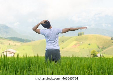 man stretching his arm in paddy field with mountain background