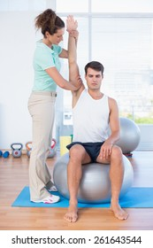 Man stretching his arm with trainer in fitness studio