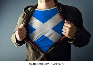 Man stretching jacket to reveal shirt with Scotland flag printed. Concept of patriotism and national team supporting.