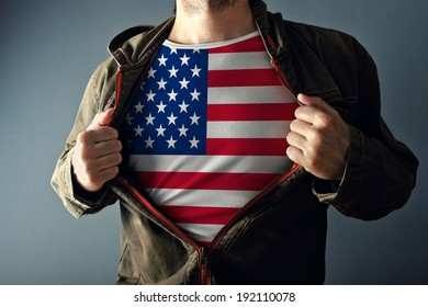 Man stretching jacket to reveal shirt with USA flag printed, concept of patriotism and American national team supporting for 4th of July