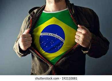 Man stretching jacket to reveal shirt with Brazil flag printed. Concept of patriotism and national team supporting.