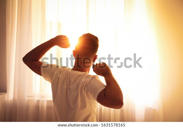 Man stretching near window at home, view from back. Lazy morning