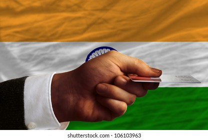 man stretching out credit card to buy goods in front of complete wavy national flag of india