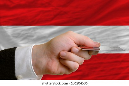 man stretching out credit card to buy goods in front of complete wavy national flag of austria
