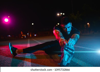 Man stretching at park while listening to music. Young man working out at nights. Healthy sport man doing stretching exercise at nights.