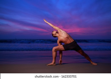 Man in stretching yoga pose on ocean beach at dusk