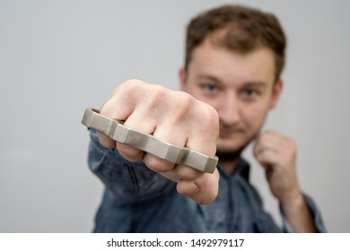 Man strikes brass knuckles on a light background, a prohibited weapon in a fight, heavy damage