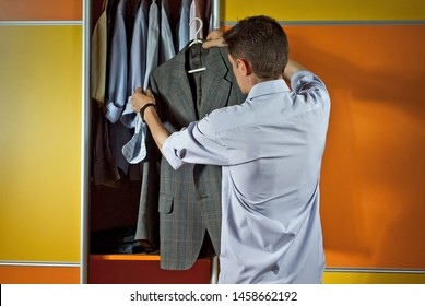 A man in a striped shirt tries clothes on the background of the closet. Yellow and orange wardrobe. The guy picks up the suit. The concept of clothing selection problem.