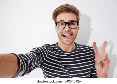 Man in striped sweater and glasses making selfie and showing peace gesture. Isolated gray background
