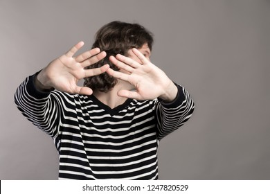 Man in striped sweater turns aside, stretching his hands forward. Pushing someone away from contact. Guy making stop hand sign palm gesture on grey background. Stay away and do not touch me concept