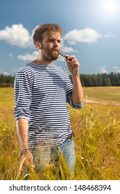 man in a striped vest on the nature in the field of e-cigarette