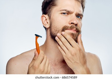 Man stroking his beard and holding a razor portrait
