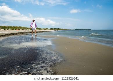 A man strolls along the Black Sea coast, Odessa region, Ukraine, June 2018