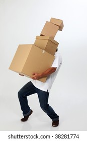 A man struggling to carry moving boxes.