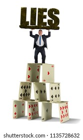 Man struggling to hold up giant stone LIES on a shaky fragile house of cards that could crumble at any moment representing the dangerous situation he is in with his self created web of deceit.