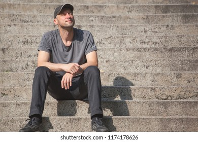 a man with a stubble in a baseball cap sits resting on the steps and enjoying the sun