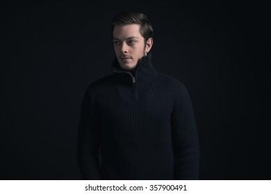 Man with stubbly beard wearing dark blue turtleneck.