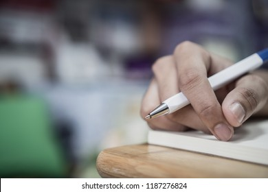 Man student taking and writing notes on notebook with pen in library at college university for homework. Education learning studying in school concept