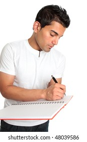 A man or student writes in a notebook