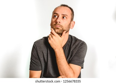 Man in studio, thoughtful hand resting on his chin, model expressions isolating white background